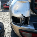 Major crash damage and dented plastic bumper